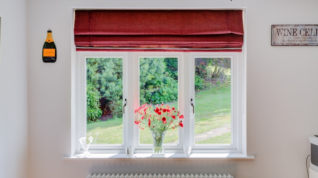 a upvc sash windows with red blind and flowers on the window sill