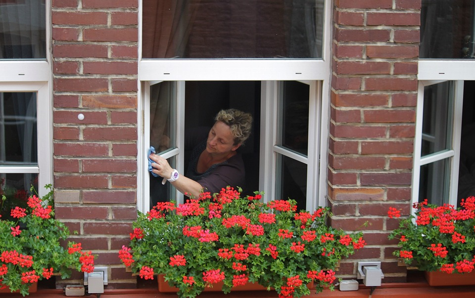 a woman washing white casement windows