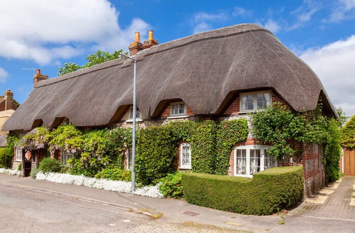 A street view of a traditional English country thatched cottage